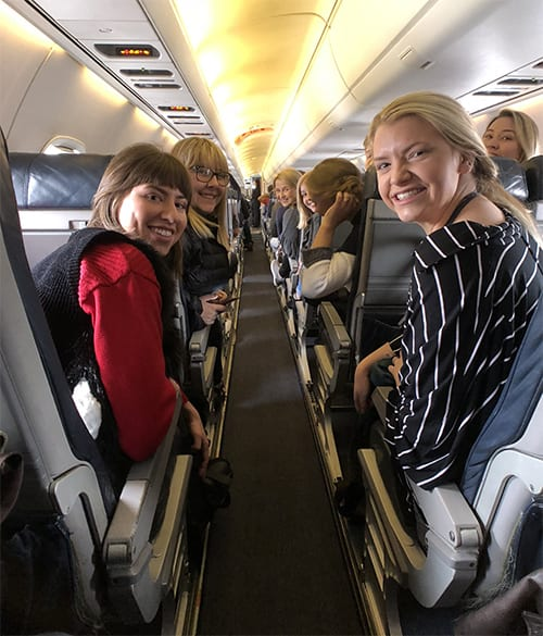 Savannah Smith, Beverly Banks, Savanna Jacoby, and others pose for a quick photo on the plane as they start their journey to New York.